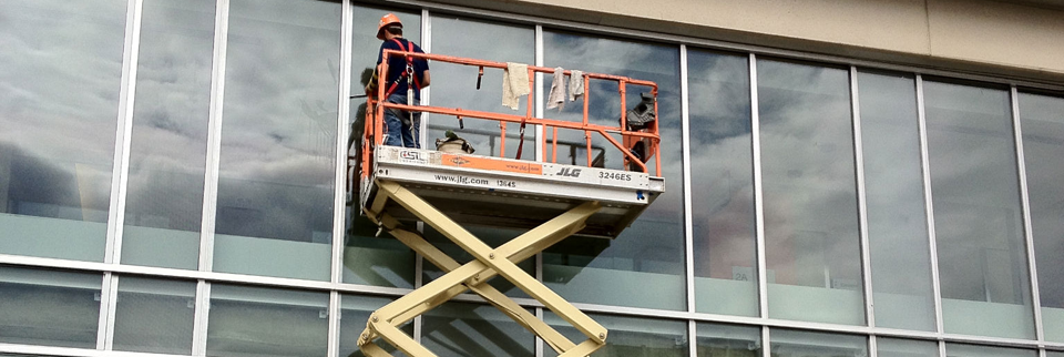worker cleaning outside glass